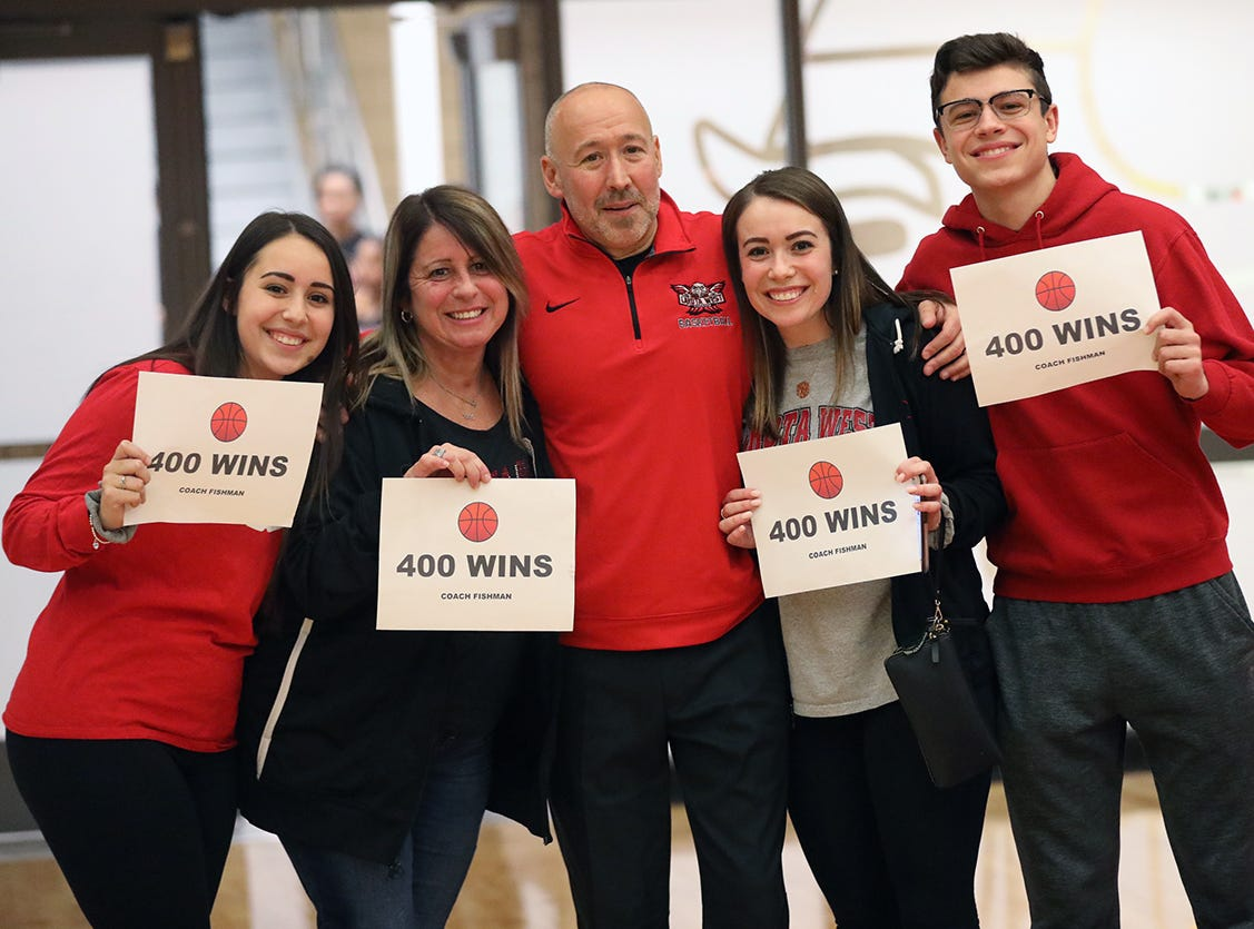 Lakota West head coach Andy Fishman and his family celebrate after he gets his 400th win over Princeton, Wednesday, Jan.16, 2019.