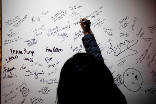 Charlene Robinson, a furloughed IRS worker, signs the wall to thank Smokin' This and That BBQ after receiving a free meal their on Thursday. Some federal government employees have been furloughed since Dec. 22.