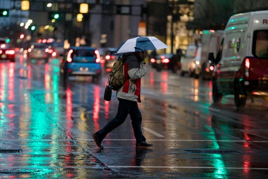 Pedestrians walk in the rain in Downtown Cincinnati, on Thursday, Jan. 17, 2019. According to the National Weather Service there is a wintery mix on Thursday ahead of possible snow storms over the weekend.