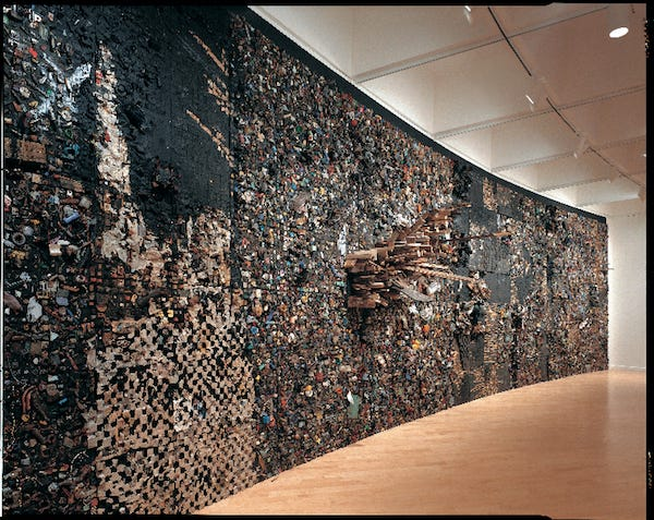 Drew is an artist known for his large wall-mounted sculptures composed of jagged tree trunks layered with thousands of segments of cut wood.