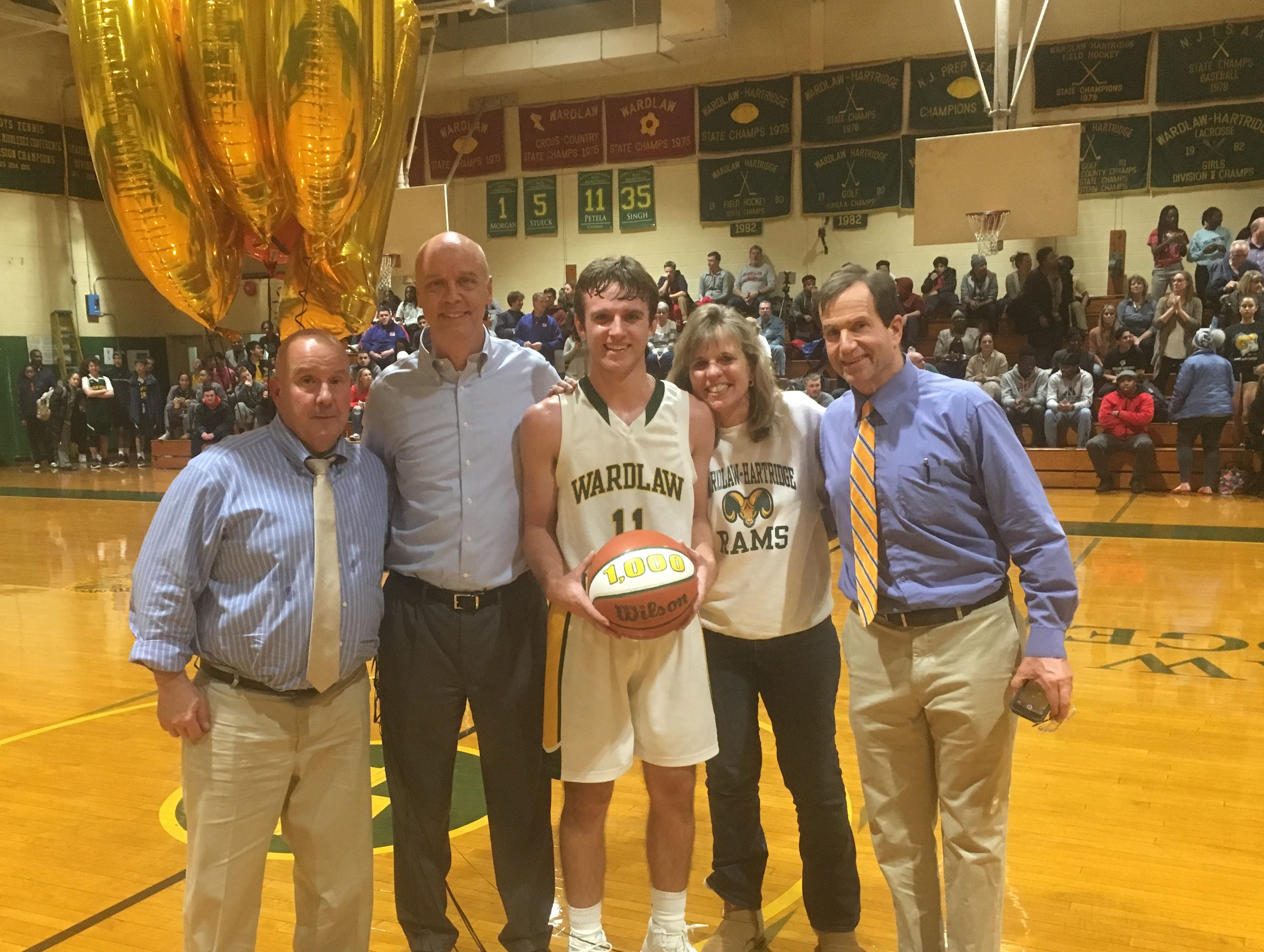 Ryan Petela celebrates his milestone with parents John and Cecilia and W+H head coach Bernie Buniak (left) and W+H athletic director Karl Miran (right).