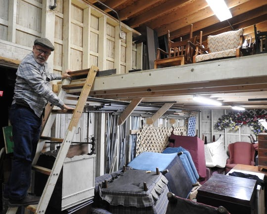 Denny Blanford climbs a ladder to a loft area used for storage of furniture at the Triple Locks Theater. A recent project extended the loft allowing for better organization and inventory of items needed for plays.