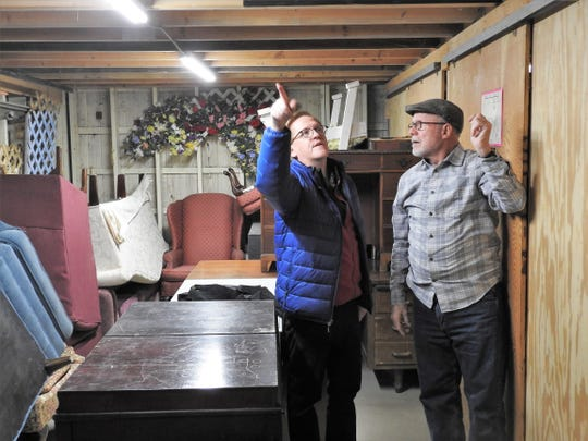 Nathan Mayse and Denny Blanford inspect a loft area at the Triple Locks Theater that was recently extended through a volunteer project. Larger items are stored underneath a platform with smaller items on top. This has allowed for better organization and inventory.