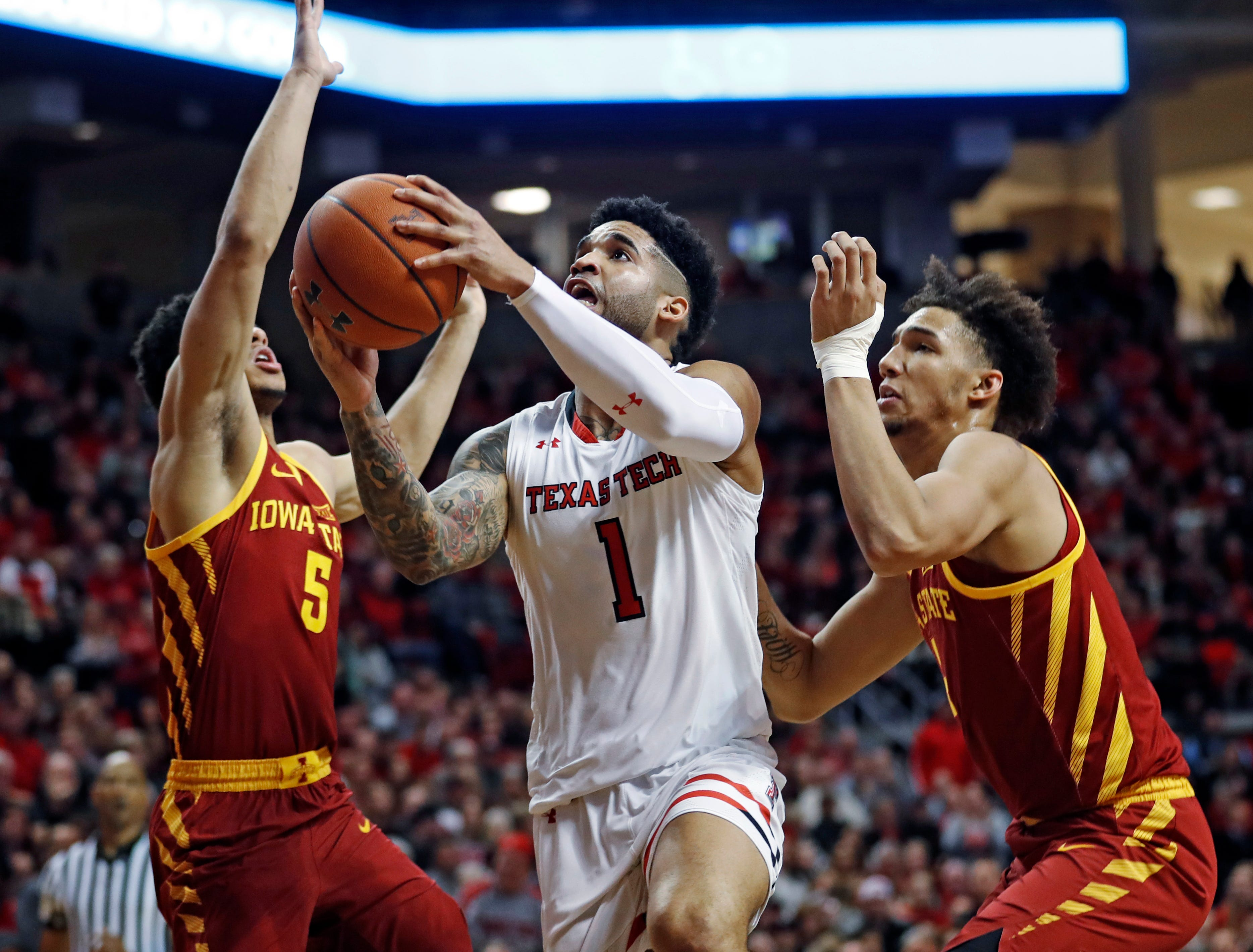 Texas Tech's Brandone Francis (1) goes to the basket between Iowa State's Lindell Wigginton (5) and George Conditt IV during the first half of an NCAA college basketball game Wednesday, Jan. 16, 2019, in Lubbock, Texas.