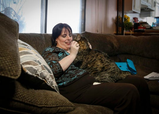 Shanna Harker pets her three-year-old tabby cat, Sox, at her home in West Des Moines on Wednesday, Jan. 17, 2019. Harker, who was sexually assaulted by a man she met on a dating app, says her pets help ease her mind as she tries to move forward in life after the assault.