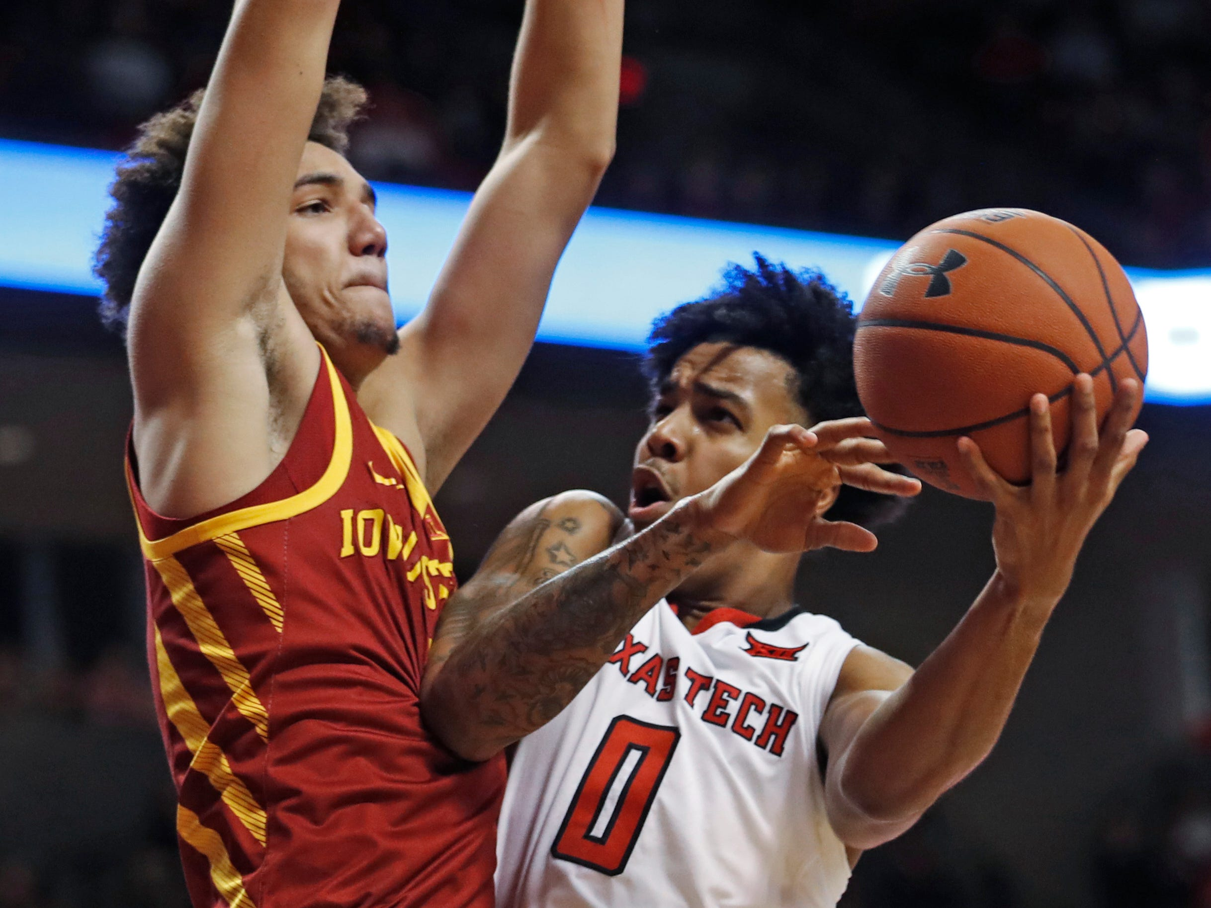 Texas Tech's Kyler Edwards (0) tries to shoot around Iowa State's George Conditt IV during the second half of an NCAA college basketball game Wednesday, Jan. 16, 2019, in Lubbock, Texas.