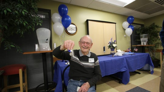 Ted Williams, 93, holds up his newly awarded Drake Relays medal. Williams placed second in the discus throw at the 1944 relays but never received a medal due to wartime rations.