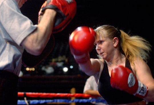 Tonya Harding spars with coach Jeff Hargis, Monday, Feb 17, 2003, during a practice boxing workout at the Grand Casino in Tunica, Miss.