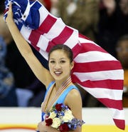 Michelle Kwan skates a victory lap during the medal ceremonies at the World Figure Skating competition in Washington, D.C. on March 29, 2003.