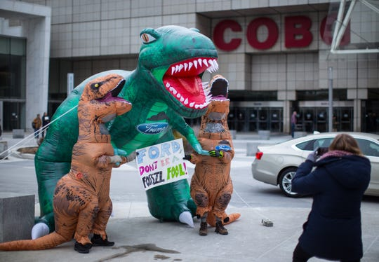 Activists wear tyrannosaurus rex costumes as they pose next to an inflatable t-rex while protesting what the protestors allege is Ford Motor Company's outsize pollution and their work with the Trump administration to roll back environmental protections outside of the North American International Auto Show at Cobo Center in downtown Detroit on Thursday, January 17, 2019.