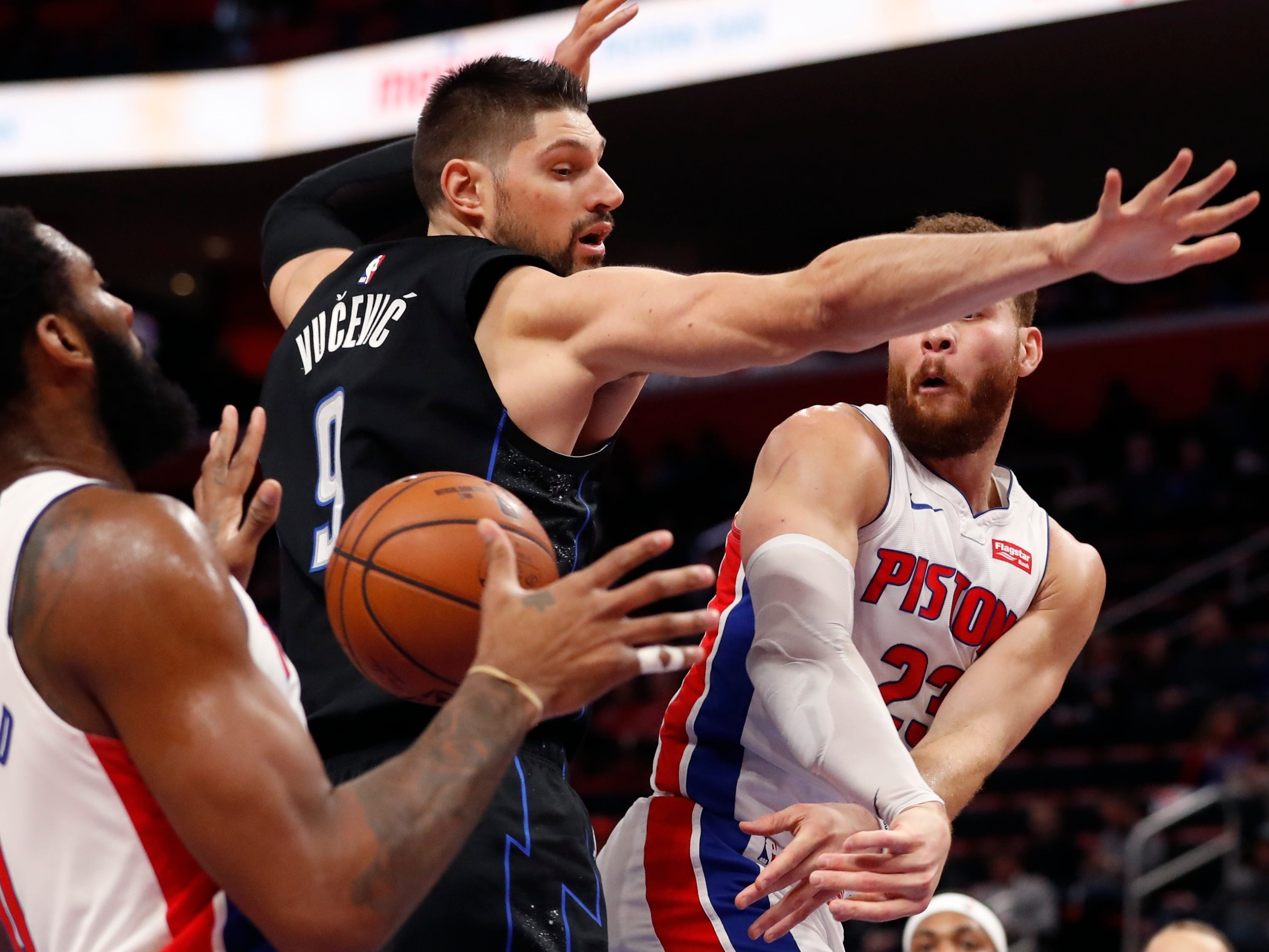 Detroit Pistons forward Blake Griffin (23) passes the ball around Orlando Magic center Nikola Vucevic (9) to center Andre Drummond (0) during the first half.