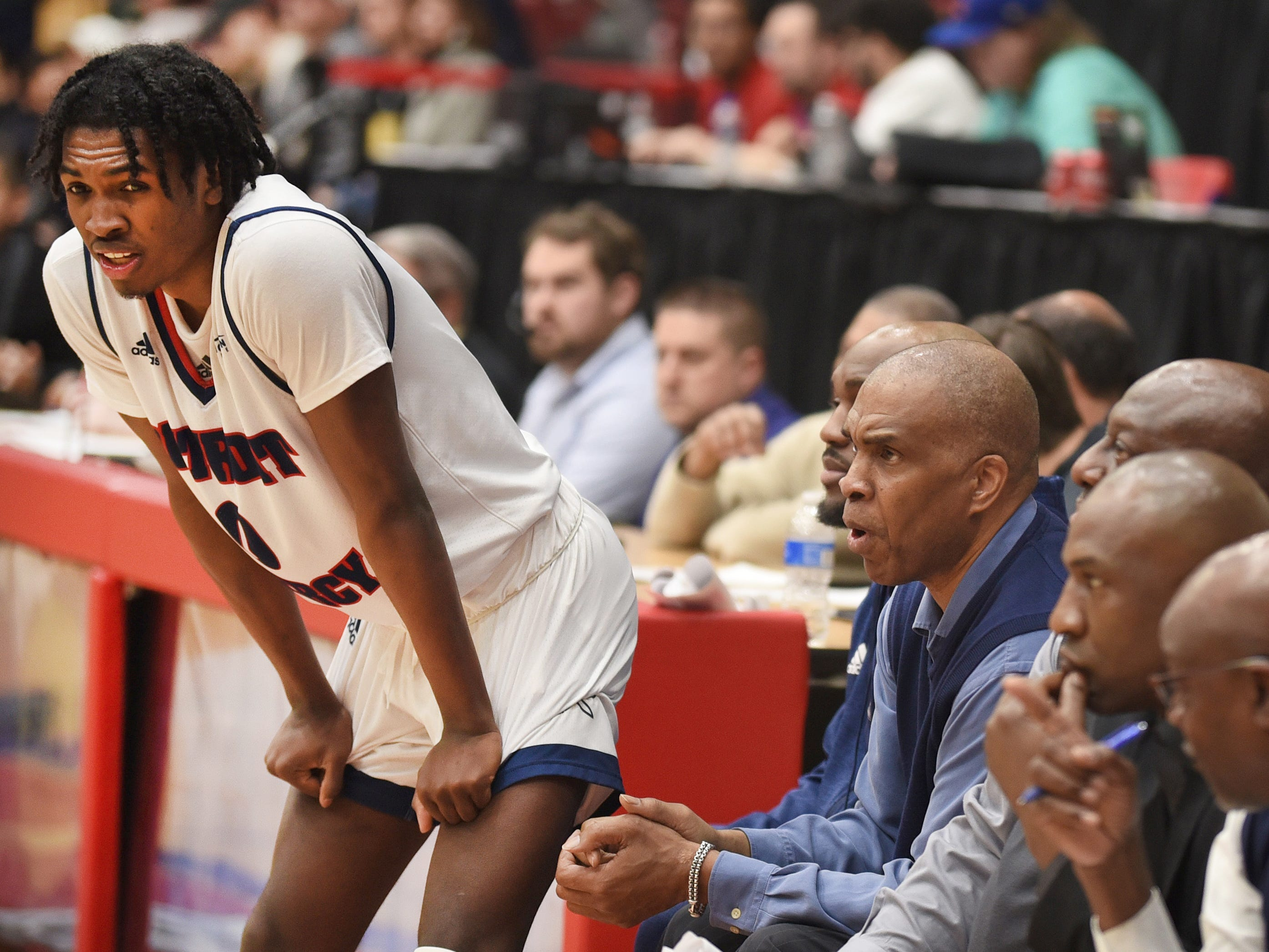 University of Detroit Mercy player Antoine Davis (left) waits to check back into the game with his father U of D head basketball coach Mike Davis (right) looking on.