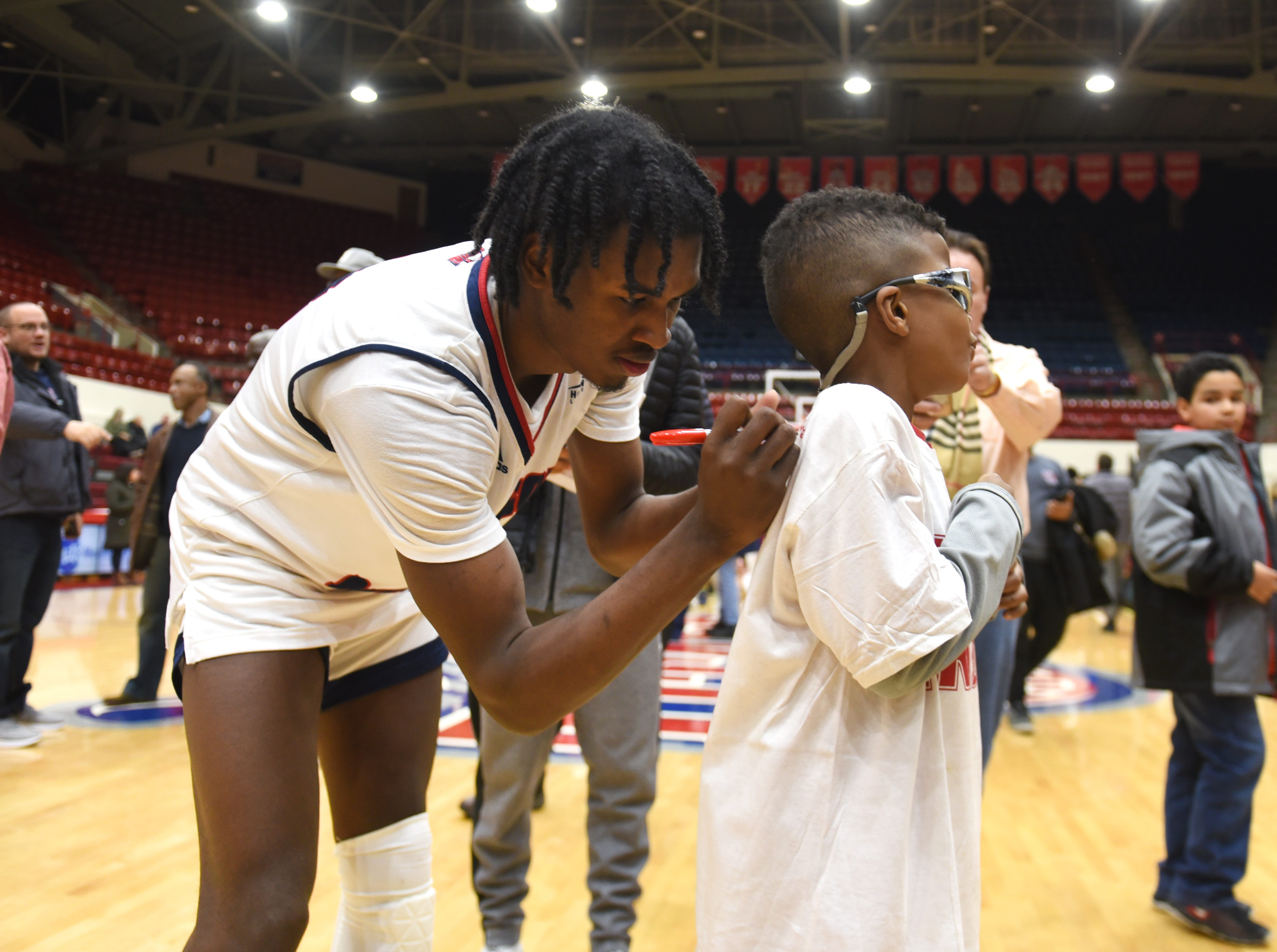 University of Detroit Mercy player Antoine Davis sign an autograph on the shirt of Joshua Grady after a victory over Milwaukee. Davis scored 32 points.