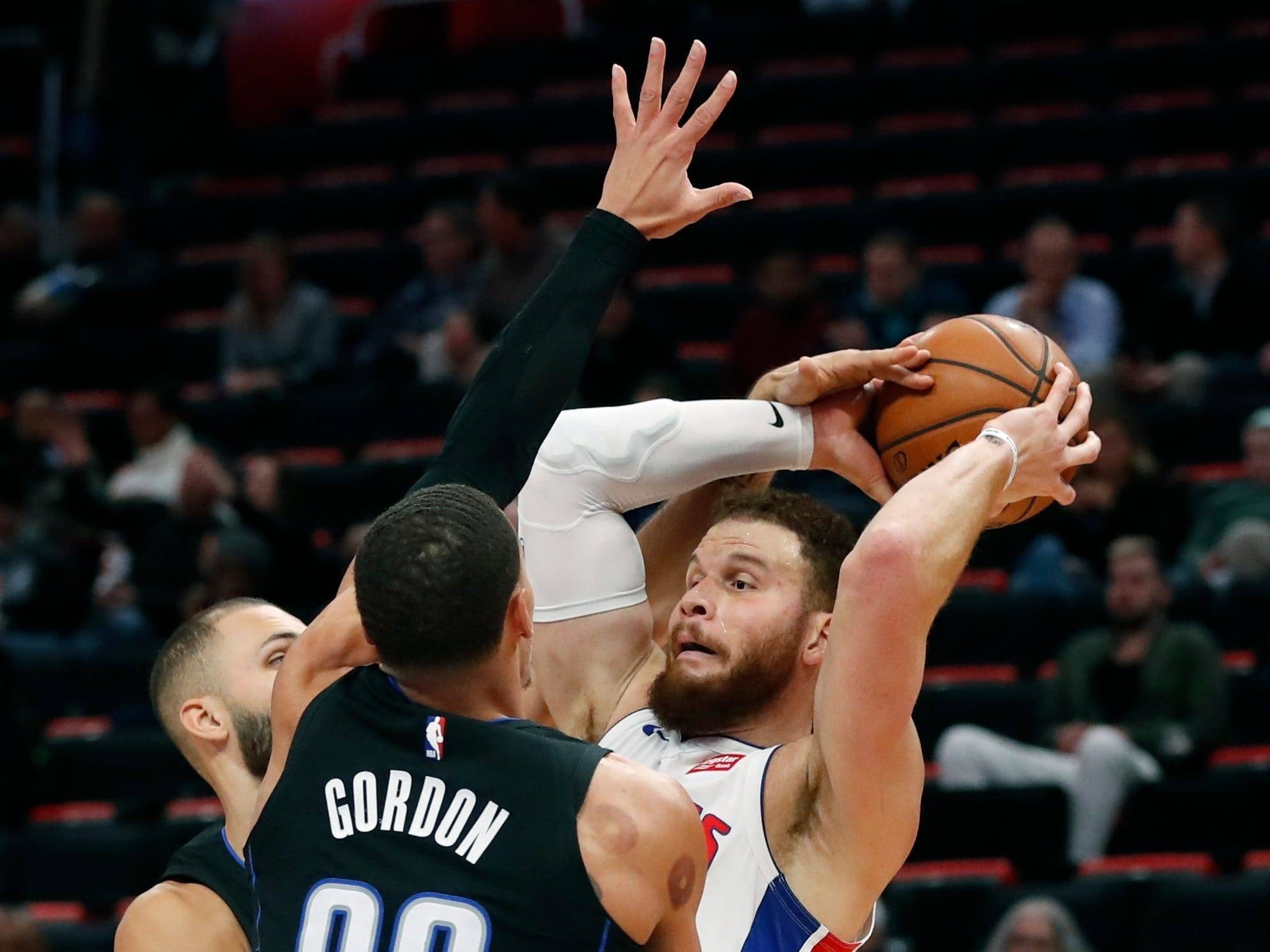 Detroit Pistons forward Blake Griffin is defended by Orlando Magic guard Evan Fournier and forward Aaron Gordon (00) during the first half.