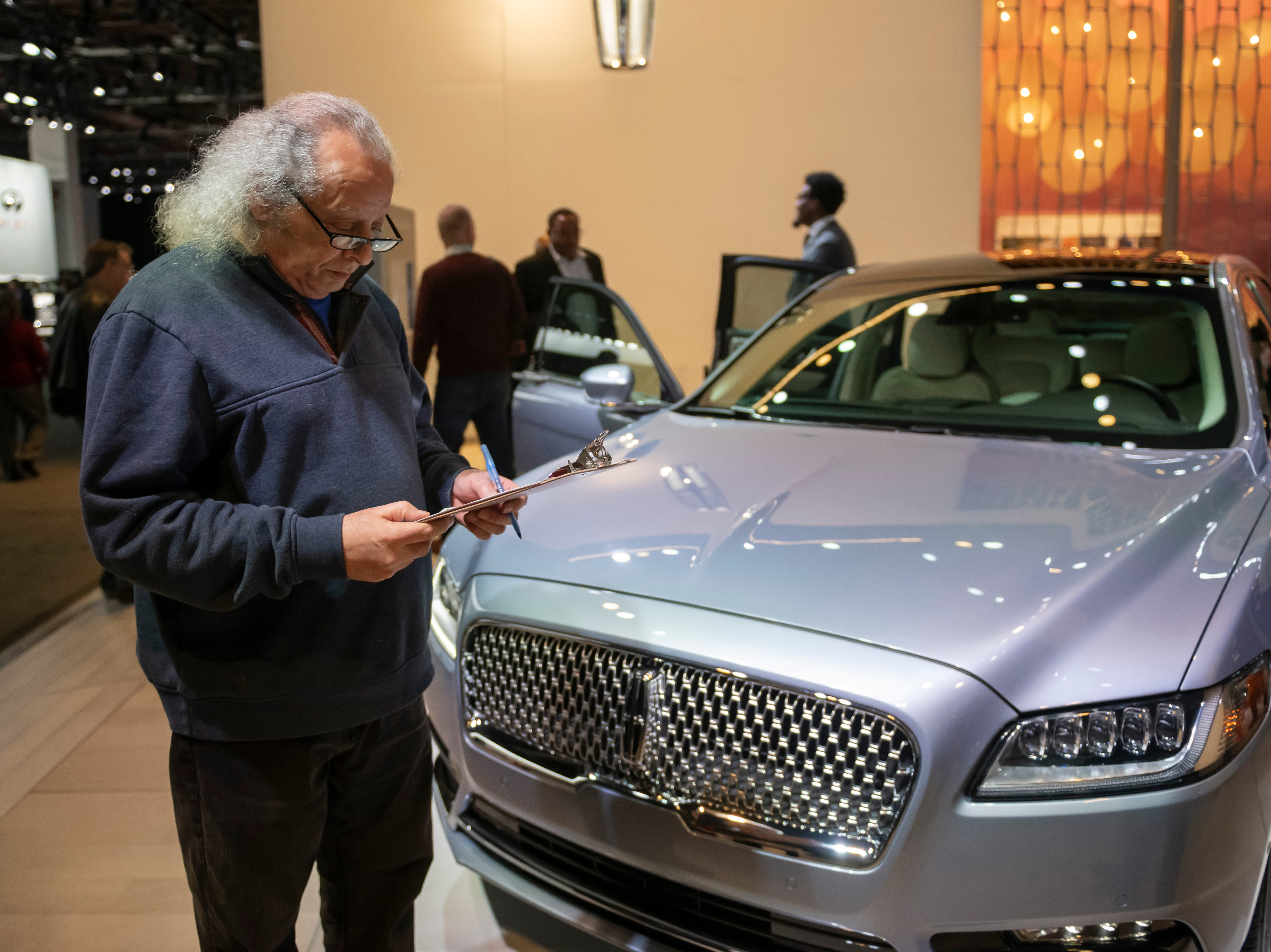 Detroit News Readers Choice awards judge Lou Hatty of Detroit goes over his notes while checking out the Lincoln Continental 80th anniversary edition.