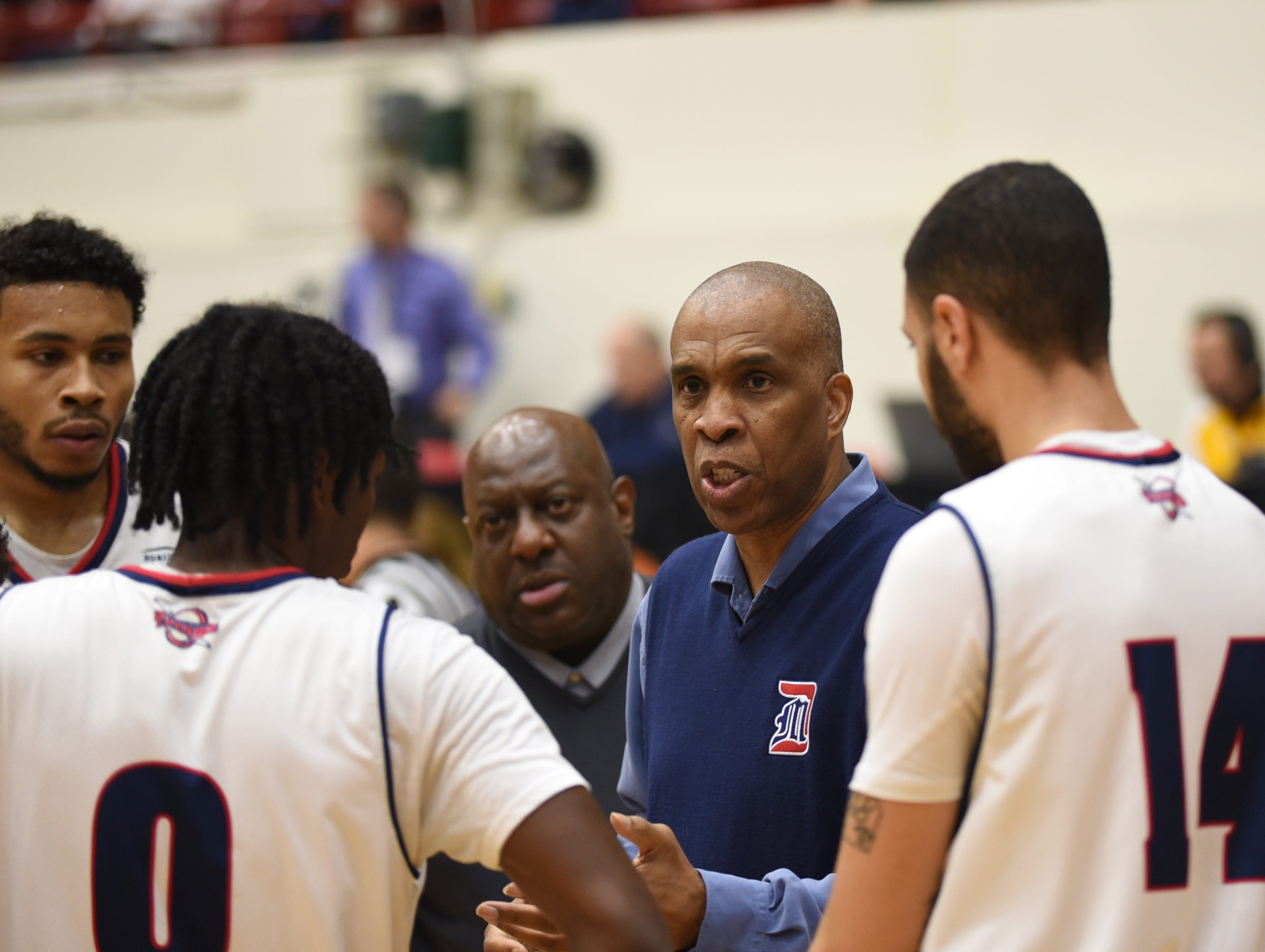 University of Detroit Mercy head basketball coach Mike Davis works with his son Antoine Davis (0) and Derrien King (14) during a timeout.