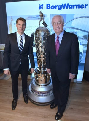 Roger Penske, right, founder and chairman of Penske Corporation, and Team Penske driver Will Power pose with the Borg-Warner Trophy before the evening session of the Automotive News World Congress at the RenCen Marriott Hotel in Detroit on Wednesday.
