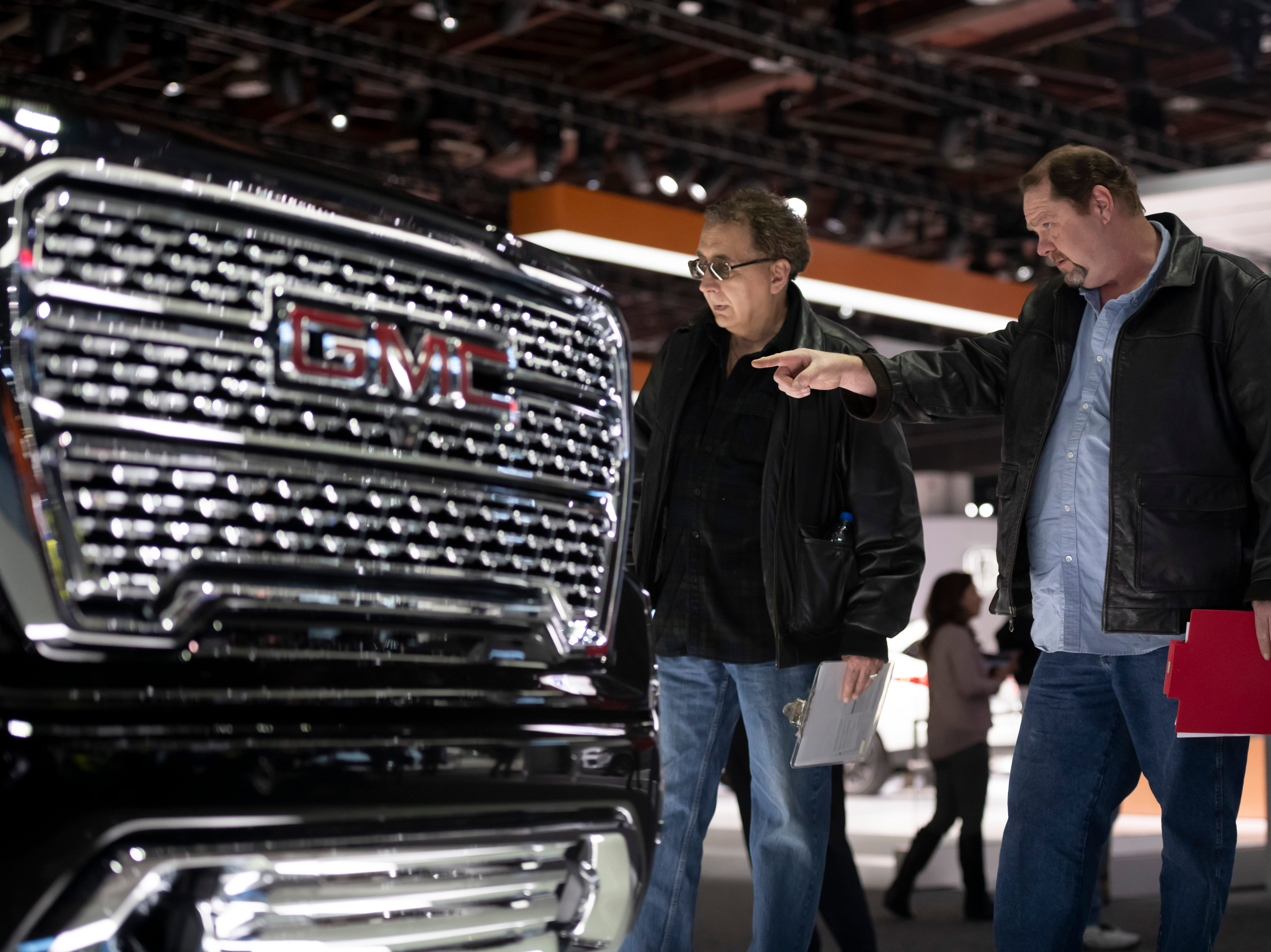 Judges Felix Fulicea of Detroit, left, and David Felker of Oak Park check out the GMC Denali Sierra.