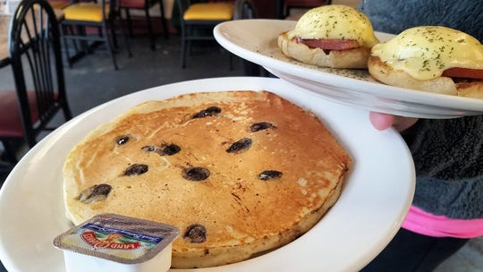 A big, fluffy blueberry ricotta pancake and eggs benedict at he Rose Hill Cafe
