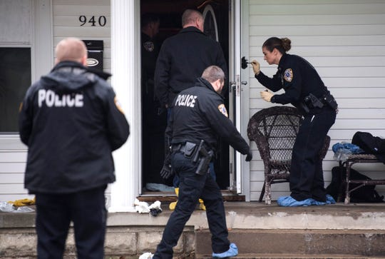 OPD officer Jennifer Haynes, far right, dusts for fingerprints on the outside of a screen door at 940 Audubon Avenue in Owensboro, Kentucky,  as police investigate a fatal shooting with at least four victims Thursday, Jan. 17, 2019.