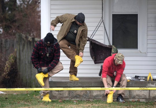 Owensboro Police Department officers put on rubber shoe covers before entering the home at 940 Audubon Avenue to investigate a fatal shooting with at least four victims Thursday, Jan. 17, 2019.