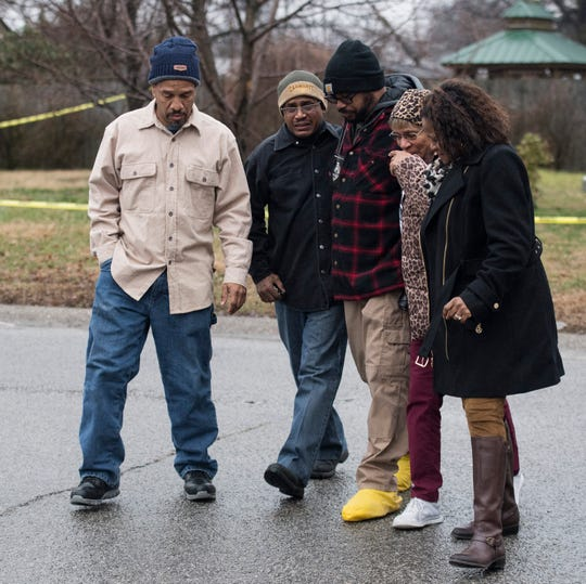 Detective Hunter Hinton walks a family across the street  after they crossed the caution tape while OPD officers investigate a fatal shooting with at least four victims at 940 Audubon Avenue in Owensboro, Kentucky,  Thursday Jan. 17, 2019.