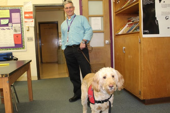 Bill Schell, Fremont Ross High School's freshman guidance counselor, walks Sloopy, the school's therapy dog Thursday. Sloopy is Schell's personal pet and has served as Fremont Ross' therapy dog since the fourth quarter of the 2017-2018 school year.