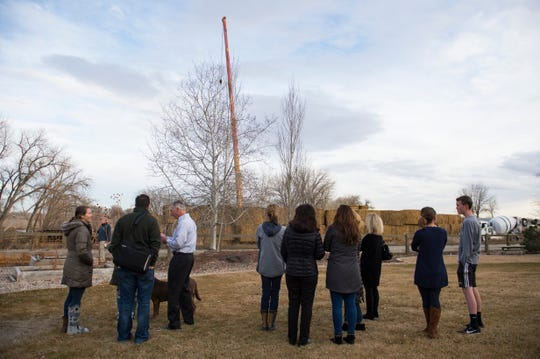 Residents of the Fossil Lake Ranch neighborhood gather in a backyard to watch construction on a cell phone tower near their properties on Wednesday.