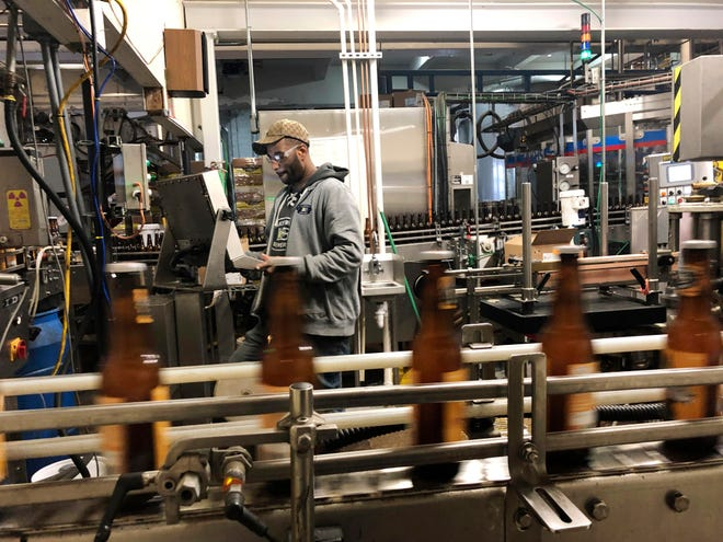 """In this Jan. 14, 2019, photo, Trevor Stevens works in the bottling room at Lakefront Brewery in Milwaukee. The federal shutdown is impacting the federal agency Alcohol and Tobacco Tax and Trade Bureau, which approves licenses for new breweries, some ingredients and labels for beers sent out of state. The brewery is now waiting for the federal agency to approve the """"My Turn: Chuck"""" beer label, so they can sell it out of state. (AP Photo/Carrie Antlfinger)"""