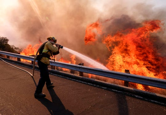 In this Nov. 12, 2018, file photo, a firefighter battles a fire along the Ronald Reagan Freeway, aka state Highway 118, in Simi Valley, Calif. A group of U.S. senators from around the American West sent a letter to President Trump warning that firefighting academies that provide required annual training for thousands of front-line fire crews are canceling classes because their federally employed instructors are on furlough. (AP Photo/Ringo H.W. Chiu, File)