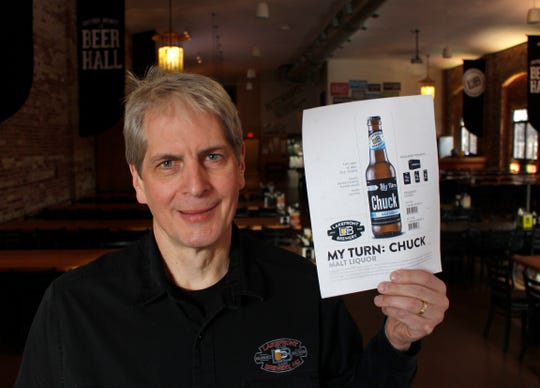 """In this Jan. 11, 2019, photo, Russ Klisch, founder and president of Lakefront Brewery, holds up a photo of """"My Turn: Chuck"""" beer. The federal shutdown is impacting the federal agency Alcohol and Tobacco Tax and Trade Bureau, which approves licenses for new breweries, some ingredients and labels for beers sent out of state. The brewery is now waiting for the federal agency to approve the """"My Turn: Chuck"""" beer label, so they can sell it out of state. (AP Photo/Carrie Antlfinger)"""