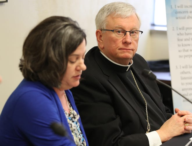 Green Bay Bishop David L. Ricken listens as Chancellor Tammy Basten, left, discusses the release of the names of 46 priests confirmed to have abused minors at the Diocese of Green Bay offices in Allouez, in January 2019.