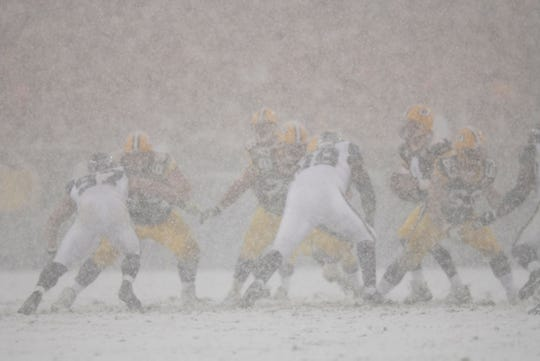 Packers quarterback Brett Favre (4) runs a play as heavy snow blankets Lambeau Field during the 2008 NFC divisional playoff game against the Seattle Seahawks. The game the following week against the New York Giants, with a game-time temperature of 1 below zero, was the third coldest in Lambeau Field's history.