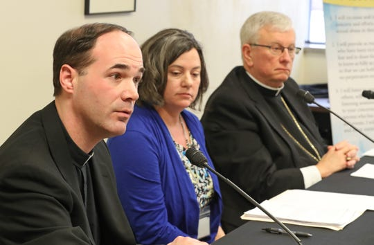 Rev. John Girotti, vicar for canonical services for the Catholic Diocese of Green Bay, discusses the release of the names of 46 priests confirmed to have abused minors at the Diocese of Green Bay offices in Allouez. At right are Bishop David L. Ricken and diocese Chancellor Tammy Basten.