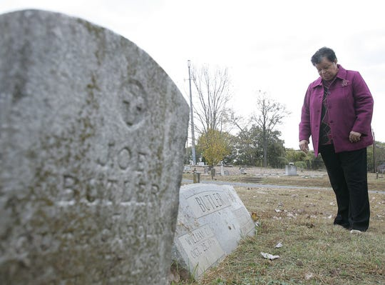 Ruth Ann Butler looks at the grave marker of distant relatives who are buried at Richland Cemetery on Nov. 16, 2005