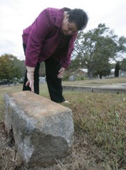 Ruth Ann Butler looks at the grave marker of Angieline Mays who is believed to be the first person buried at Richland Cemetery on Nov. 16, 2005.