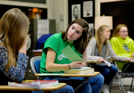 Our Lady of Lourdes seventh grader Isis Haslem, right, works with classmate Caroline Hermiller during Lori Pupura's theology class, Thursday morning.