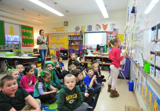 Wendy Baker looks on as her class of first graders work on an assignment at Our Lady of Lourdes on Thursday morning.