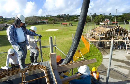 In this file photo, employees of 5M Construction Corp. pour concrete into a beam for one of three pavilions at Ypao Beach Park.