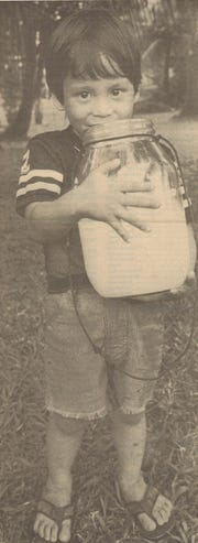 John Peredo, son of tuba maker Camilo Peredo, holds up a glass jar of tuba in this 1986 photo.