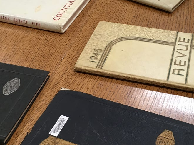 Historic yearbooks are set out in the Henderson County Public Library for people to view as part of an exhibit celebrating 150 years of public education here.
