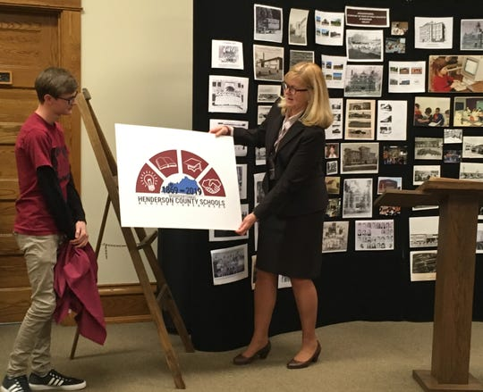 Henderson County High School Senior Nicholas Nixon and Henderson County School Superintendent Marganna Stanley unveil the logo that Nixon designed to celebrate 150 years of public education in Henderson County.