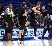 Jordan Bohannon, right, celebrates with walk-on Austin Ash after the Hawkeyes slayed Penn State, 89-82, with a game-finishing 8-0 run.
