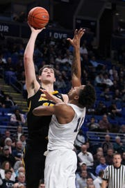 Iowa center Ryan Kriener shows off his offensive arsenal with a hook shot over Penn State's Lamar Stevens on Wednesday. Kriener had a season-high 15 points in that Hawkeye win. He has been the team's best shooter during a four-game winning streak.