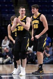 As the seconds wind down, Iowa's Connor McCaffery (30) and Luka Garza grin inside the Bryce Jordan Center.