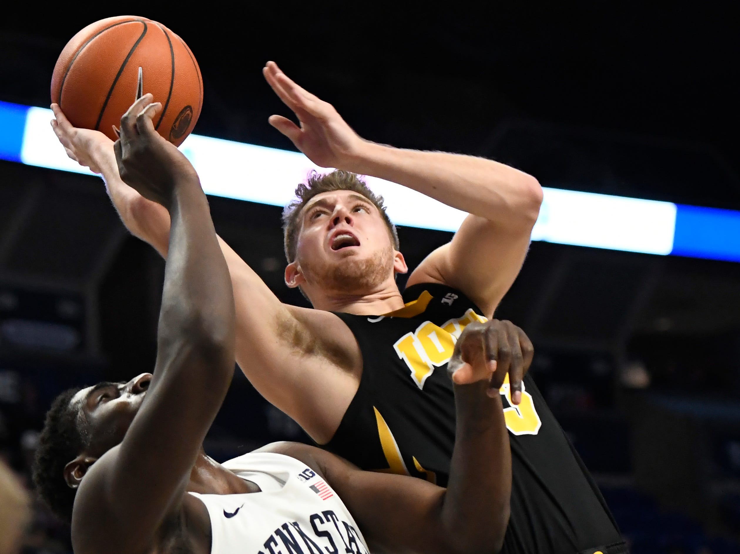 Iowa guard Jordan Bohannon (3) takes a shot over Penn State forward Mike Watkins (24) during the first half of an NCAA college basketball game Wednesday, Jan. 16, 2019, in State College, Pa.