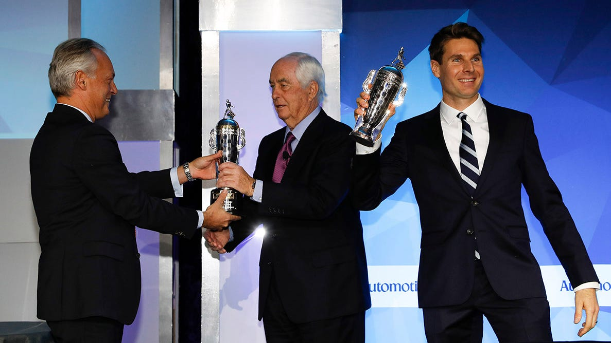 Roger Penske and Will Power are presented with their Baby Borg-Warner trophies by BorgWarner President and CEO Fred Lissalde.