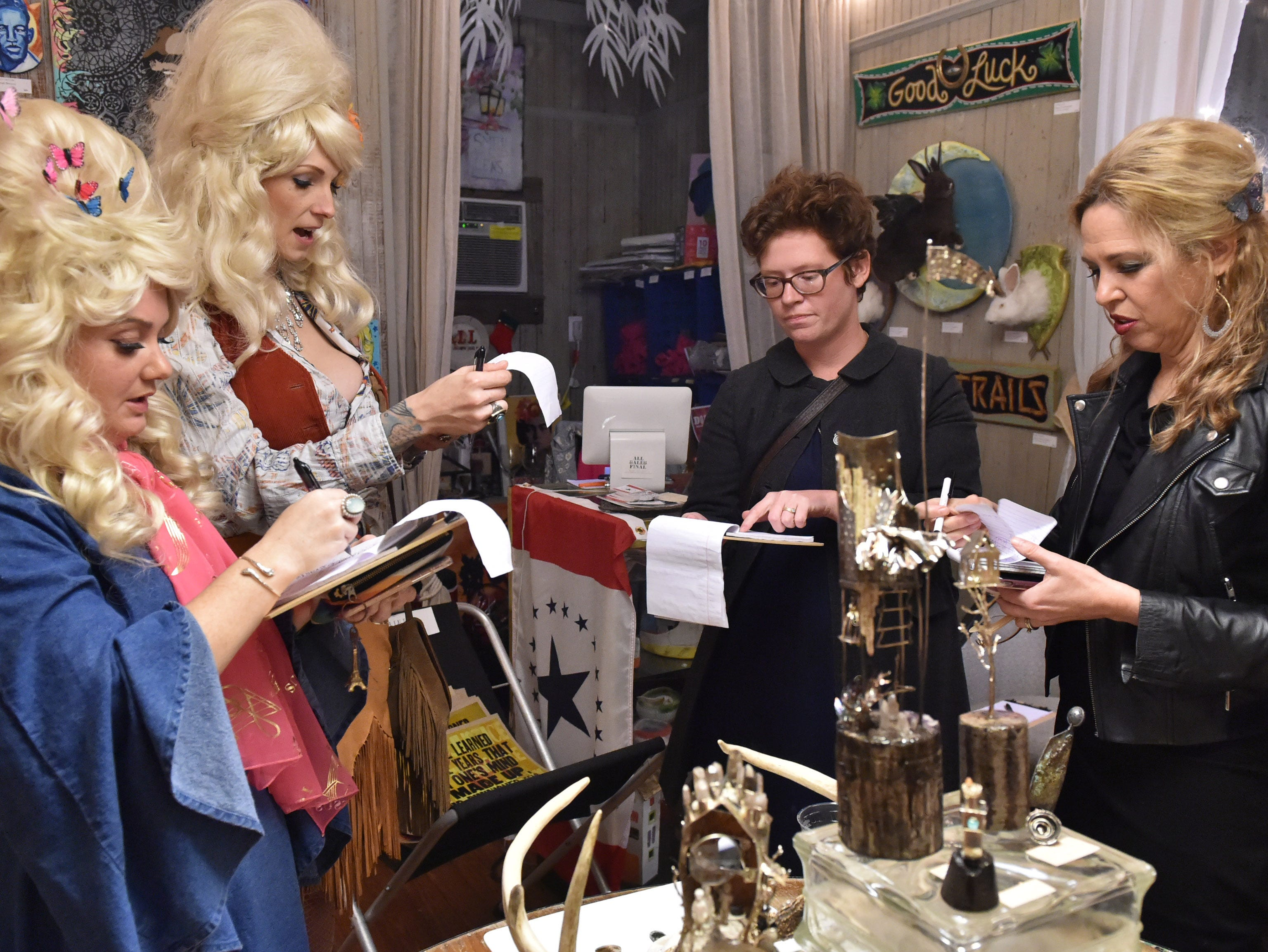 Left to right, Dolly Should look-a-like contest judges Grace Wilson Birch, Bunny Cunningham, Marshall Blevins & Margaret McMullan tally the results of the event in the showroom of Smith & Lens gallery in old town Bay St. Louis. Saturday, Jan. 12, 2019.