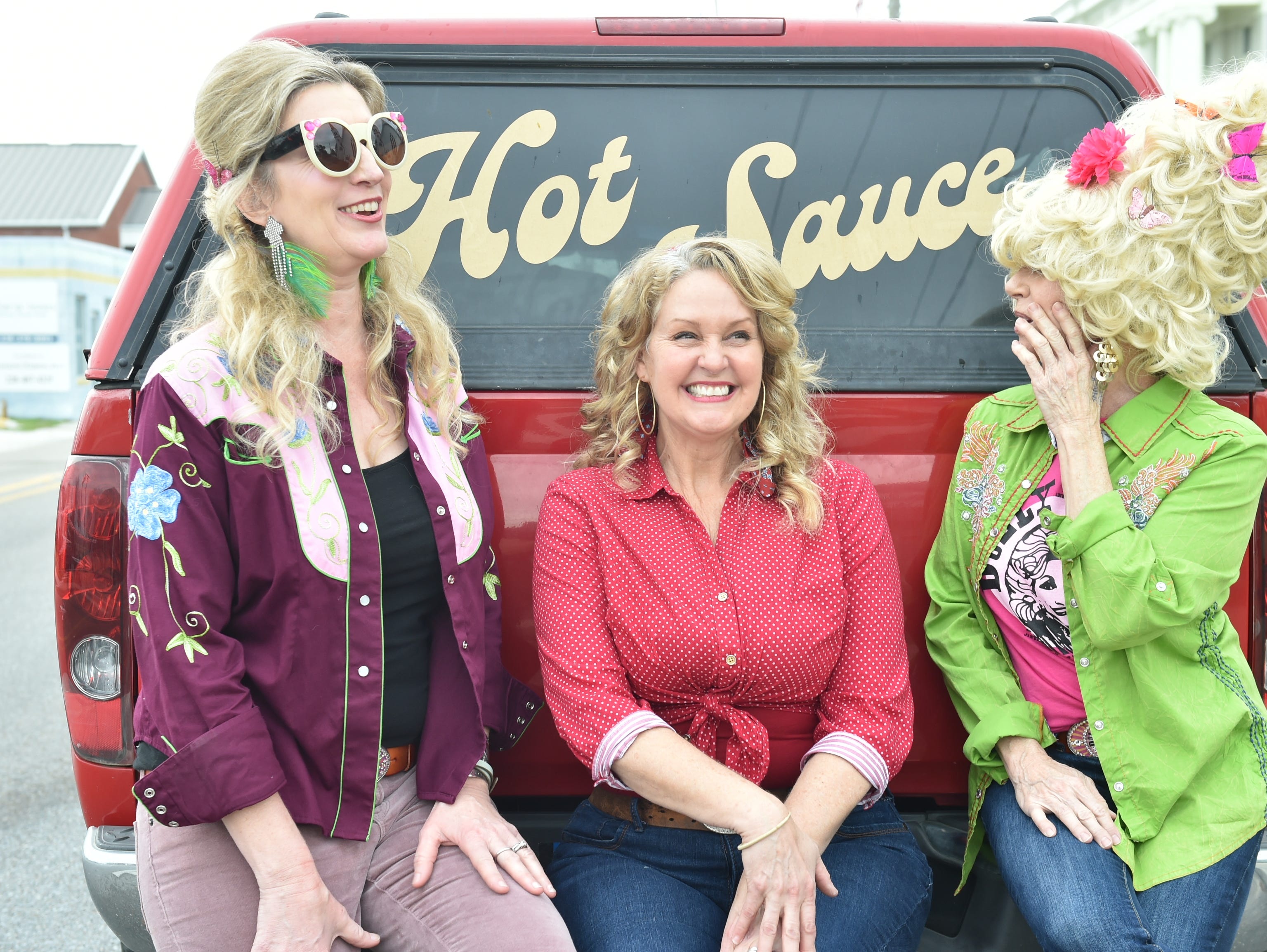 Artists and Dolly Should festival runners Ann Madden, Alicein Schwabacher and Sandy Maggio hangout on the bumper of a truck during the 4th annual Dolly Should festival-a Dolly Parton-themed event. The hope is Parton will come visit Bay St. Louis. Saturday, Jan. 12, 2019.