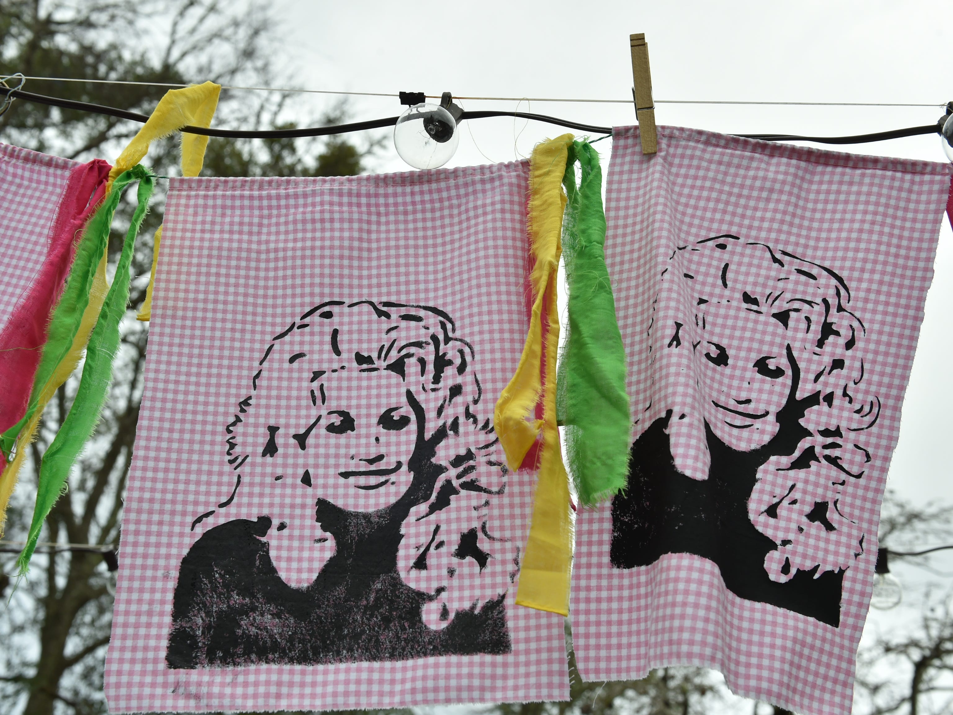 Banners embellished with images of the Dolly Should festival muse Dolly Parton hang in the courtyard between the Mockingbird Care and Smith & Lens in Bay St. Louis. Saturday, Jan. 12, 2019.